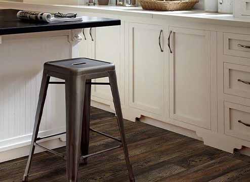 Dark wood-look vinyl flooring planks in kitchen
